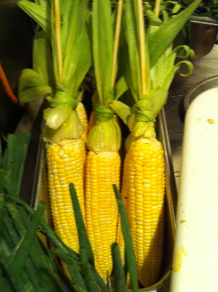 First local sweet corn from Three Sisters Garden, ready for wood grill. Topped w crema, queso añejo, chile